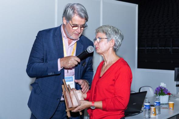 Kristel Leclercq, artiste choisie par la Club des CSE Citoyens, explique comment elle a réalisé ce livre en céramique, livre qui sera offert à Thierry Jeantet avec le traditionnel trophée en baccarat - Photo : Jacques Martin -